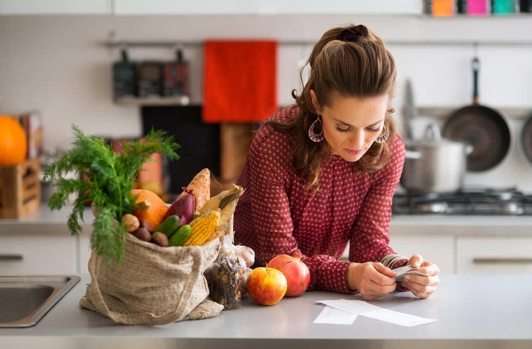 Woman with groceries looking at receipt